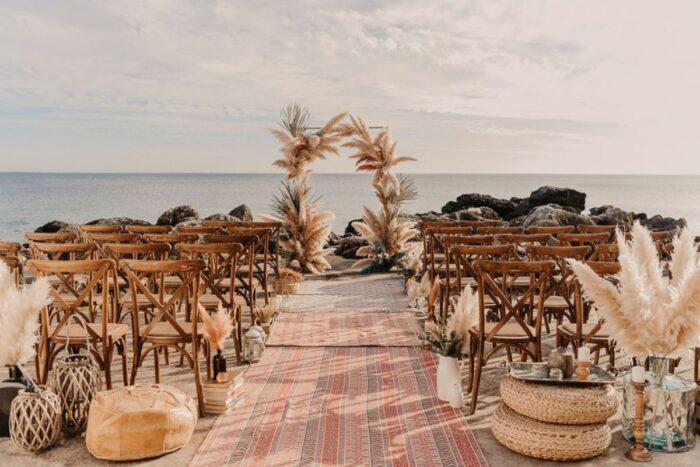 casamento boho scandi na praia com um arco com pampas tapete étnico no corredor