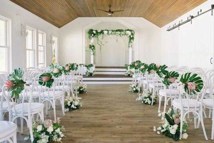 cerimónia civil com cadeiras brancas e arranjos florais com folhas tropicais monstera e proteas