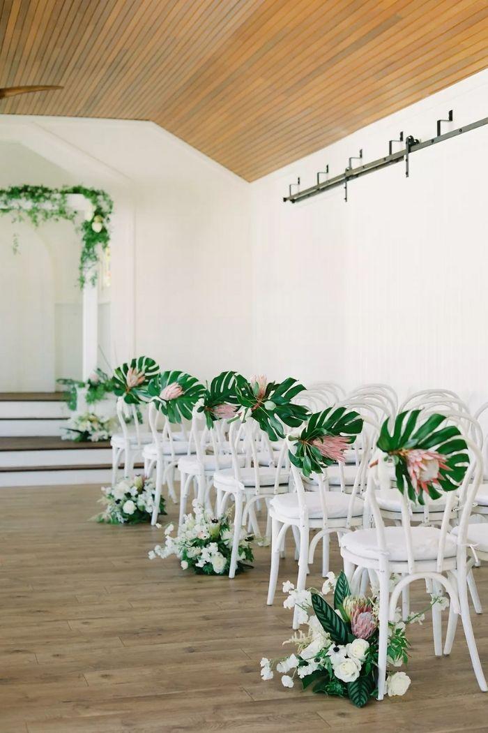perspetiva de fundo de cerimónia civil com cadeiras brancas e arranjos florais com folhas tropicais monstera e proteas