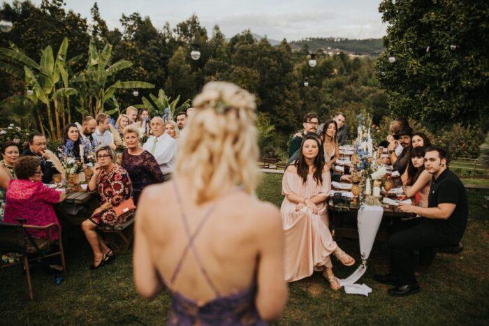 rapariga loira de costas a fazer discurso de casamento ao ar livre glamping wedding