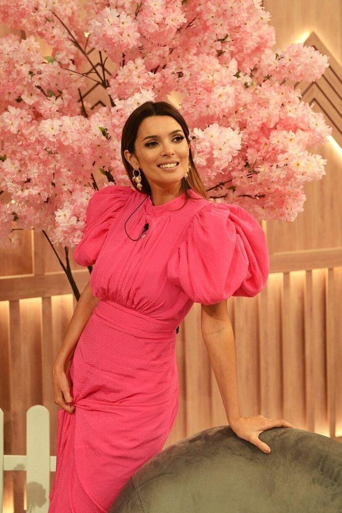 Maria Cerqueira Gomes com vestido rosa rosa fucsia cenário parede em madeira com flores rosa