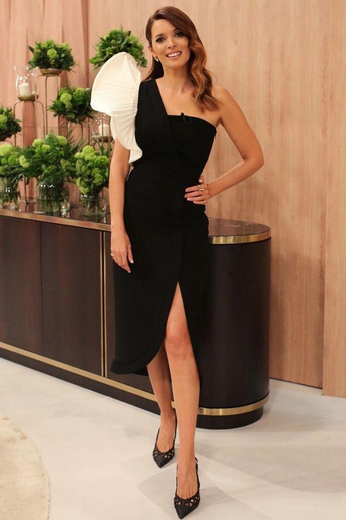 maria cerqueira gomes vestido preto um ombro com folho XL em branco cenário TV cómoda atrás requintado