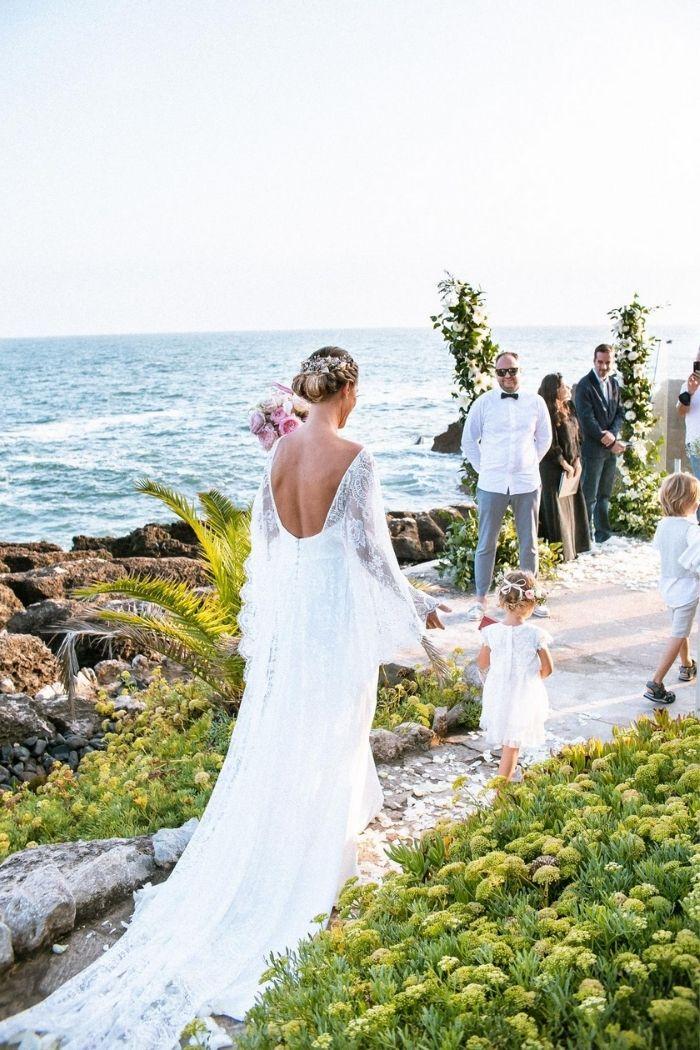 ao lado do mar, noiva chega a cerimónia de casamento com crianças noivo à espera