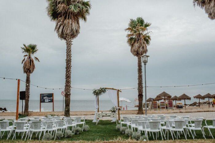 casamento em frente à praia com cadeiras de esplanada sagres e altar vintage arranjos florais para decorar o corredor da cerimónia