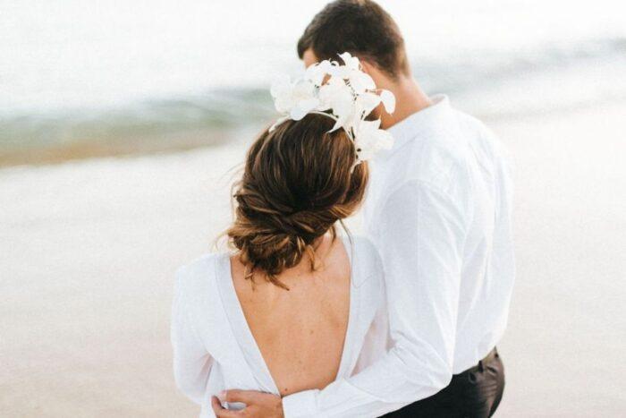 casal de noivos de costas vestidos de branco na praia
